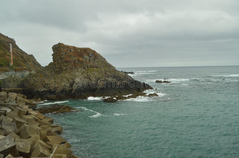 Scogliere verdi con le onde del mare che si rompono contro le loro rocce alla spiaggia di Las Llanas un giorno piovoso 29 luglio  immagine stock