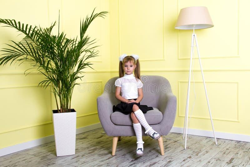 Scolara che si siede sulla poltrona grigia lussuosa nello stile classico nella stanza con la palma nel vaso e nella a fotografia stock