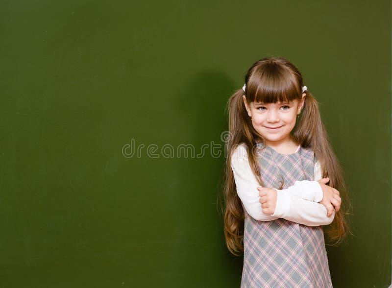 Scolara che sta nella classe vicino ad una lavagna verde fotografie stock libere da diritti