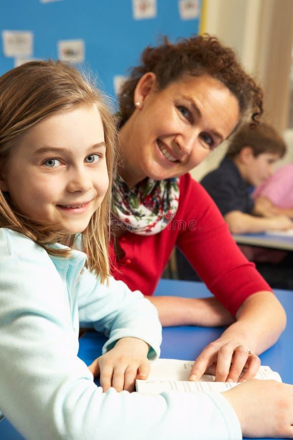 Scolara che studia nell'aula con l'insegnante immagine stock libera da diritti