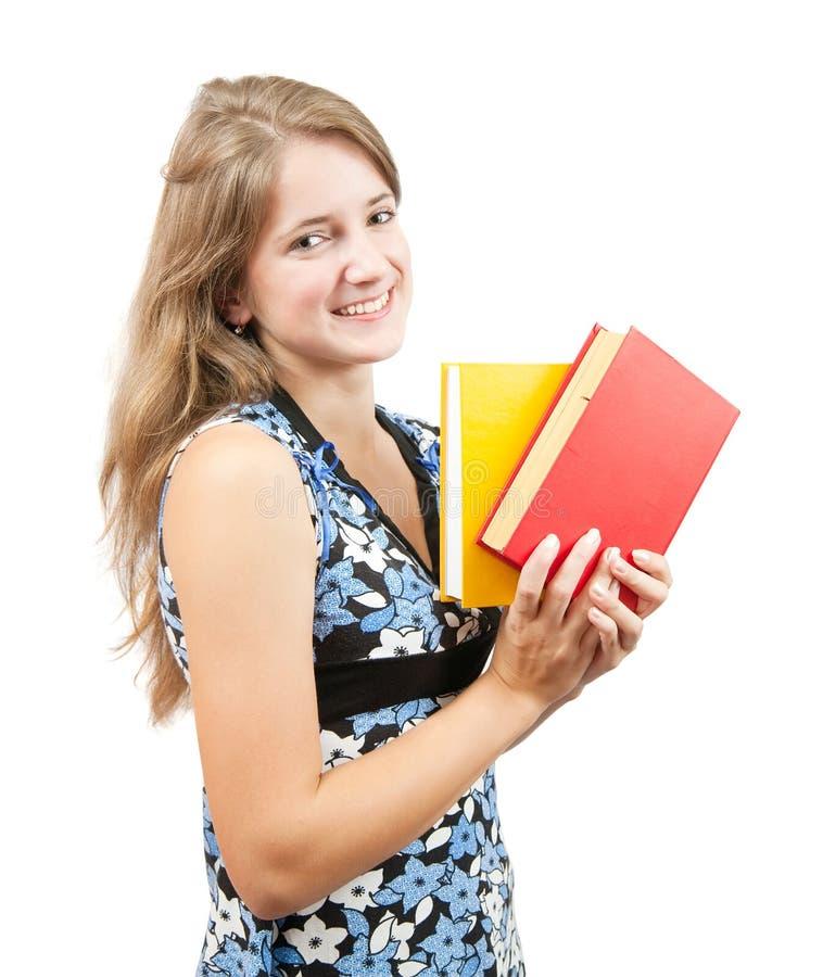 Scolara con i libri sopra bianco immagini stock