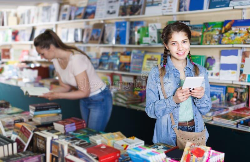 Scolara con la compressa dello schermo al deposito di libri fotografia stock