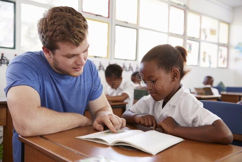 Scolara d'aiuto al suo scrittorio, fine dell'insegnante volontario su immagine stock