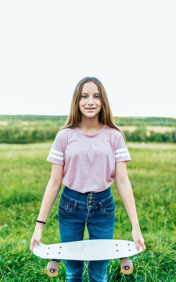 Scolara della bambina 12-16 anni, sulla via di estate nel parco Nelle mani di tenuta del pattino fotografia stock libera da diritti