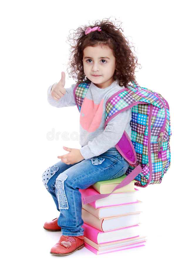 Scolara della bambina che si siede sui libri fotografie stock