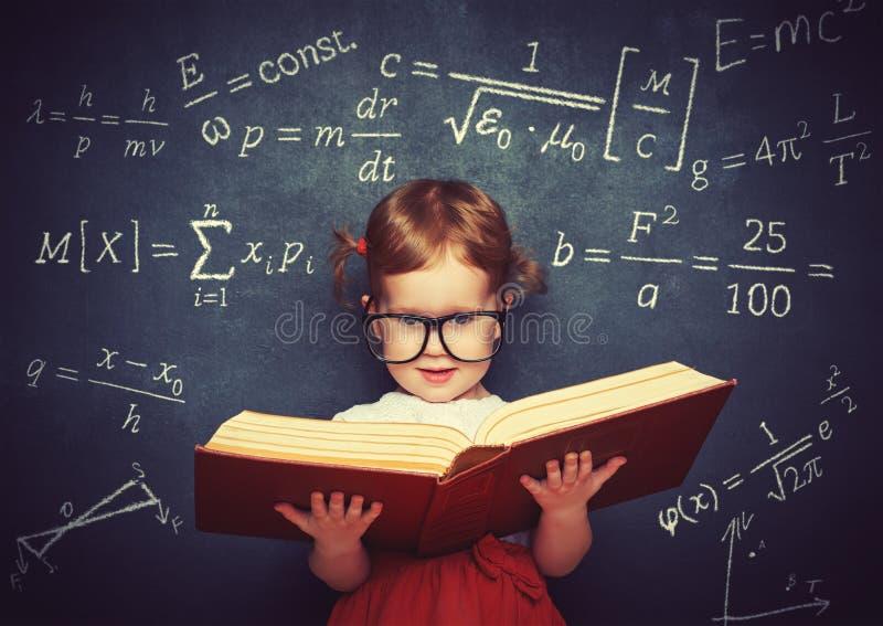 Scolara della bambina del Wunderkind con un libro dal blackboar immagine stock