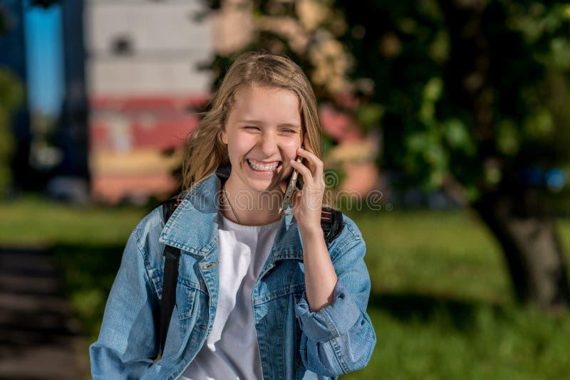 Scolara della ragazza che parla sul telefono, di estate in natura, sorridente felicemente, emozionalmente felice In sue mani tien immagine stock libera da diritti