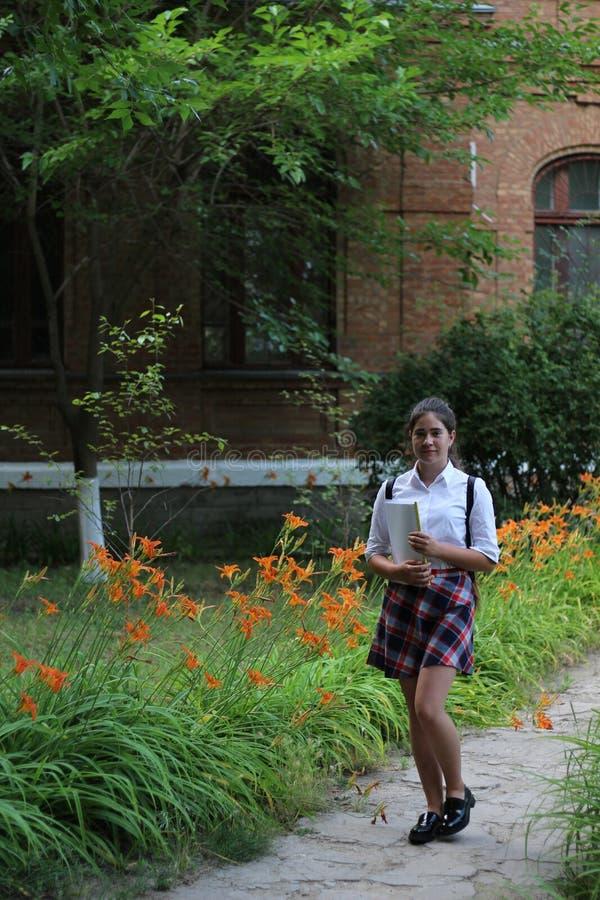 Scolara della ragazza con una cartella in sue mani immagini stock libere da diritti