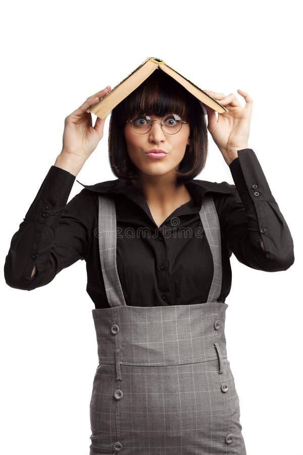 Scolara divertente del brunette che si nasconde sotto il tetto fotografia stock