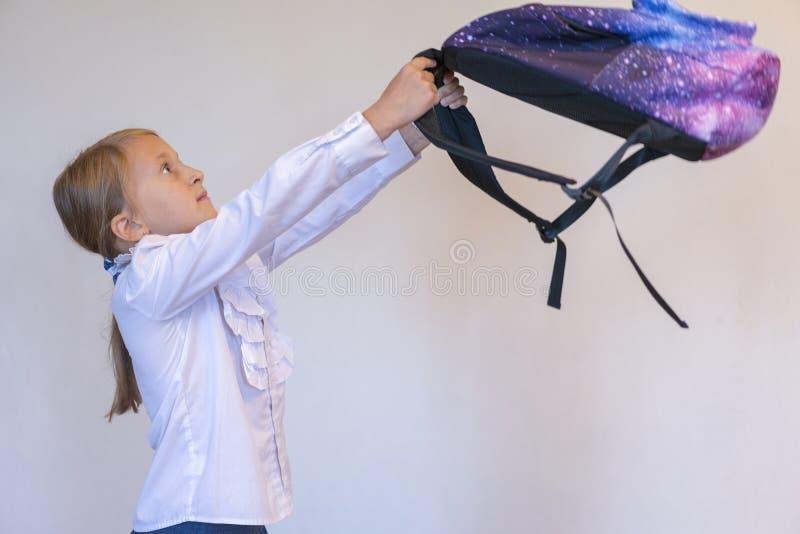 Scolara felice con lo zaino Bambina divertente con il grande zaino che salta e che si diverte contro la parete del turchese Conce fotografie stock libere da diritti