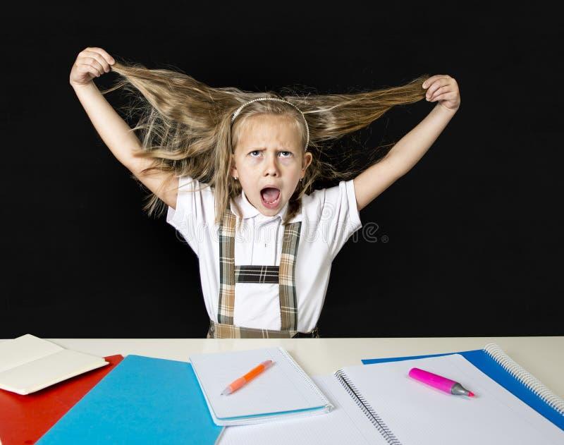 Scolara minore pazza che si siede sullo scrittorio nello sforzo che lavora facendo compito che tira i suoi capelli biondi pazzi fotografia stock