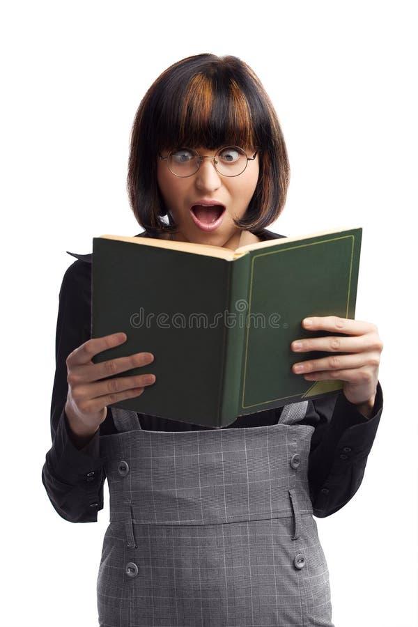 Scolara scossa del brunette che osserva nel libro fotografie stock
