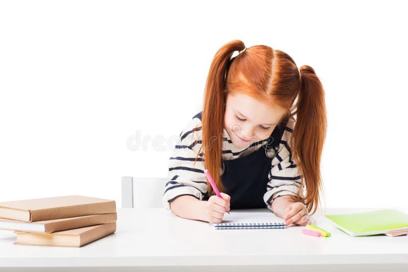 scolara sorridente sveglia che assorbe taccuino mentre sedendosi alla tavola fotografia stock