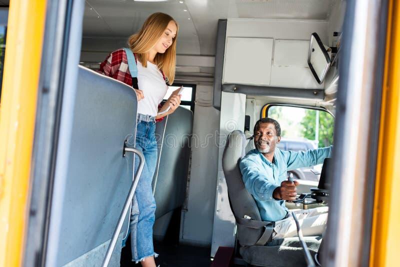 scolara teenager che cammina in scuolabus mentre sorridere senior del driver fotografia stock libera da diritti