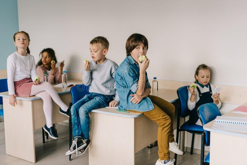 scolari che mangiano le mele all'attimo dell'aula fotografia stock