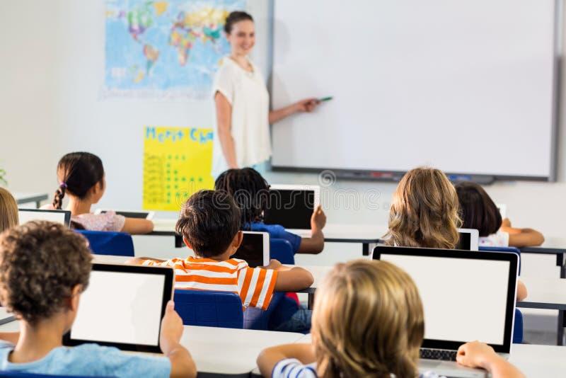 Scolari che per mezzo delle compresse digitali contro l'insegnante femminile che insegna loro fotografia stock