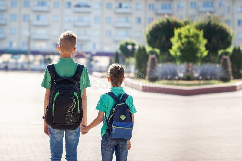 Scolari con andare a scuola degli zainhi Bambini e istruzione nella città fotografie stock