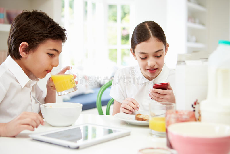 Scolari con la compressa ed il cellulare di Digital alla prima colazione fotografie stock