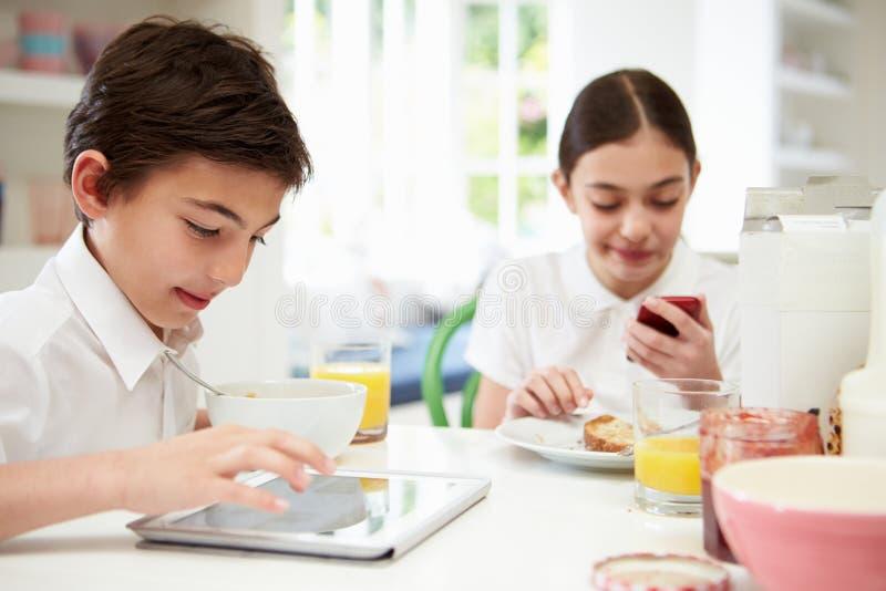 Scolari con la compressa ed il cellulare di Digital alla prima colazione immagini stock