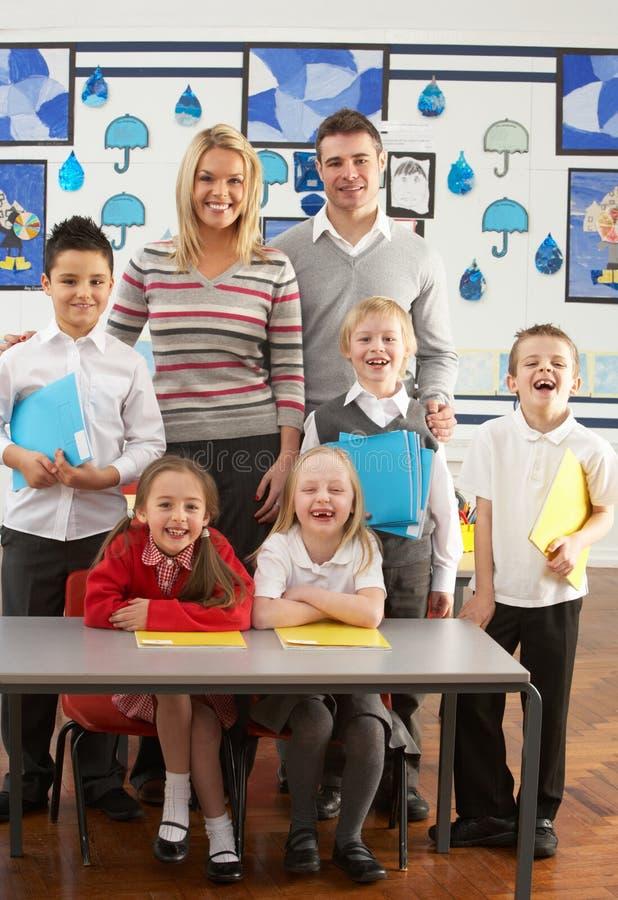 Scolari ed insegnante primari allo scrittorio immagini stock libere da diritti