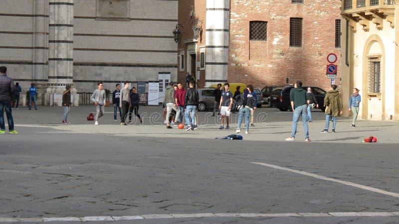 Scolari italiani che giocano a calcio nel contesto urbano immagine stock libera da diritti