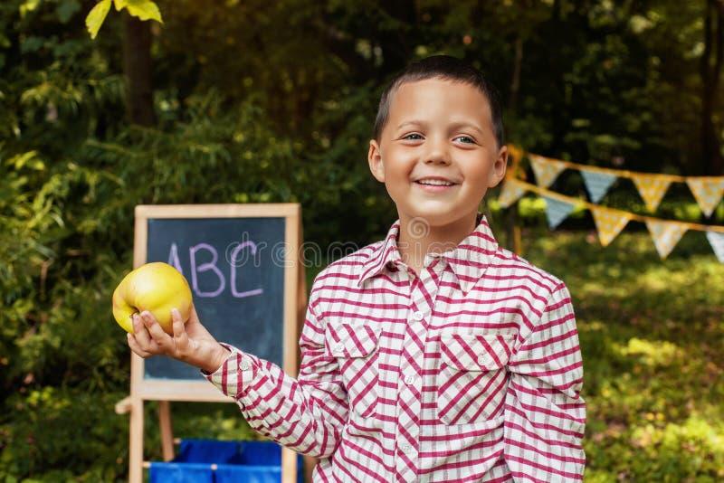 Scolaro allegro con una mela Di nuovo al banco Il concetto di istruzione, scuola, infanzia fotografia stock