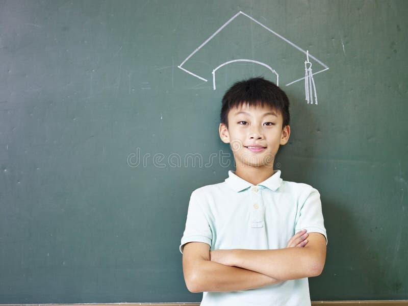 Scolaro asiatico che sta sotto un cappuccio di laurea gesso-disegnato fotografia stock