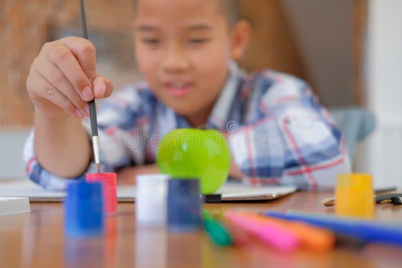 scolaro asiatico del bambino del ragazzo del bambino che tiene painti del disegno del pennello fotografia stock