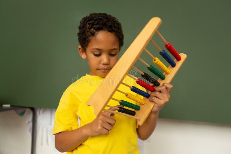 scolaro che impara matematica con l'abaco in un'aula fotografia stock