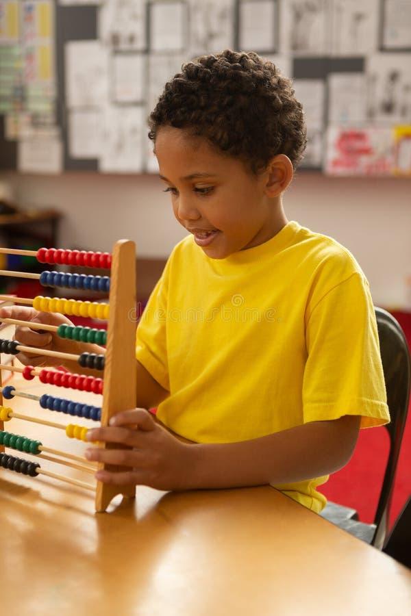 scolaro che impara matematica con l'abaco in un'aula fotografia stock libera da diritti