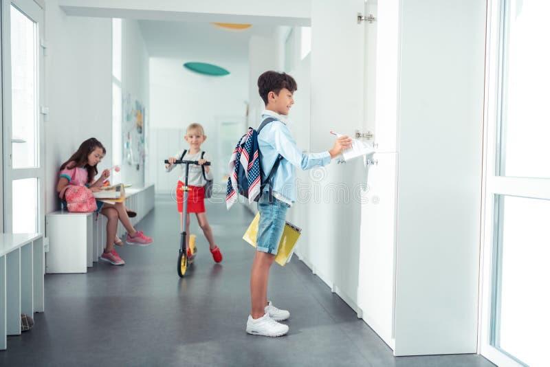 Scolaro che prende taccuino dall'armadio che sta nel corridoio della scuola immagine stock