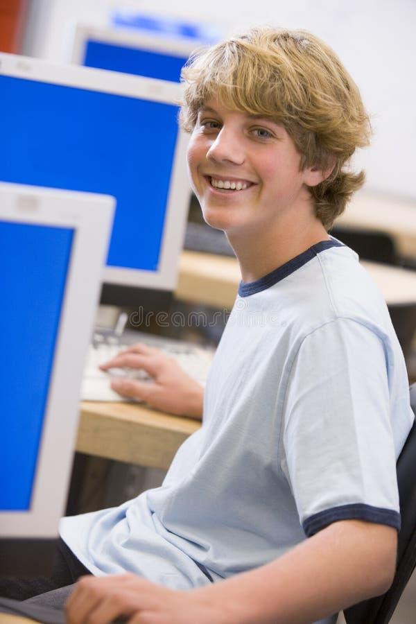 Scolaro che si siede davanti ad un calcolatore immagine stock libera da diritti