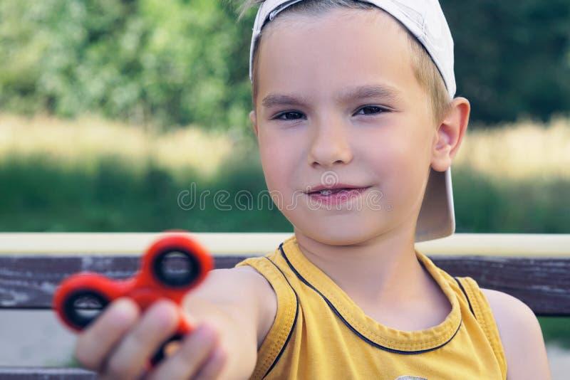 Scolaro che tiene il giocattolo popolare del filatore di irrequietezza - ritratto alto vicino Bambino sorridente felice che gioca fotografia stock