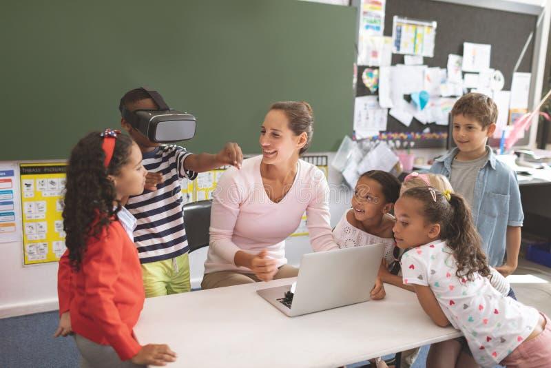 Scolaro che utilizza la cuffia avricolare di realtà virtuale alla scuola nell'aula con i suoi compagni di classe ed il suo insegn fotografie stock libere da diritti