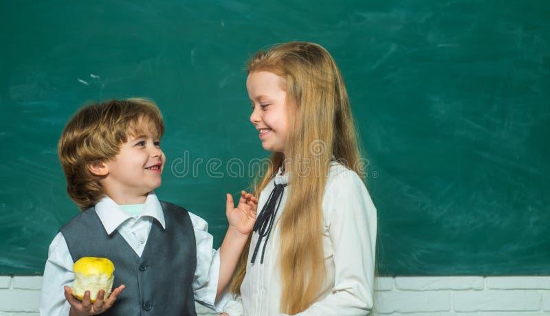 Scolaro d'aiuto della scolara dell'insegnante con la lezione Istruzione Scherza la formazione Ragazza e ragazzo con l'espressione fotografie stock libere da diritti