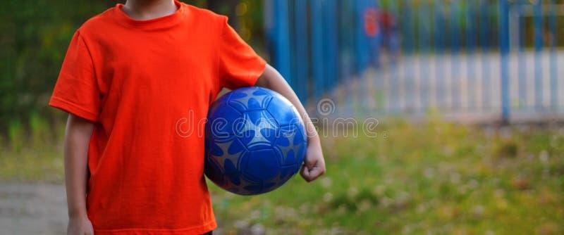 Scolaro del ragazzo che gioca a calcio sul campo da giuoco fotografie stock