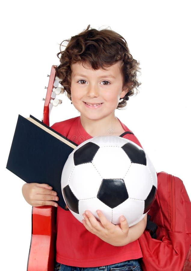 Scolaro di Bussy con una palla, una chitarra e un libro immagini stock libere da diritti