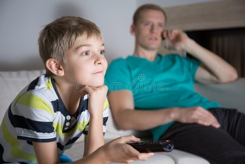 Scolaro dipendente a guardare TV fotografia stock
