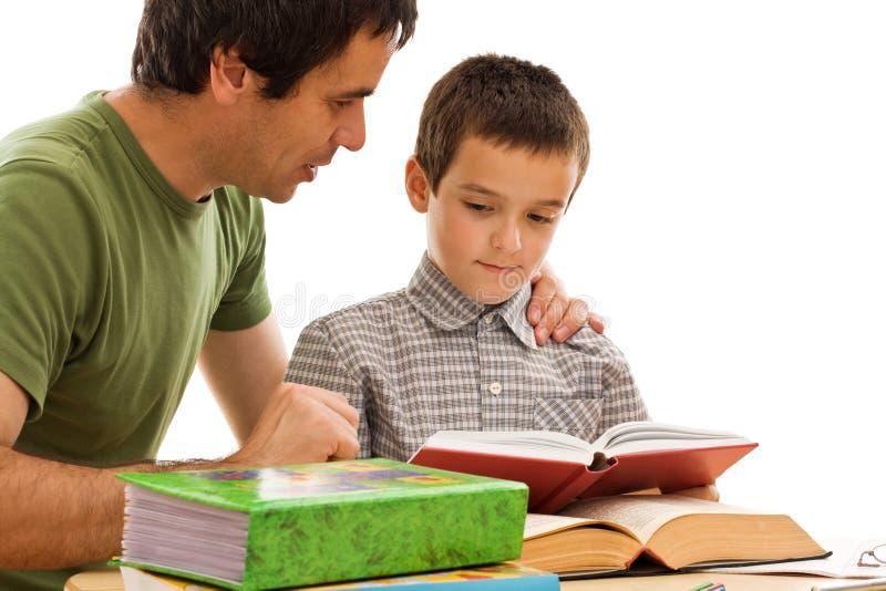 Scolaro ed il suo apprendimento del padre immagini stock libere da diritti