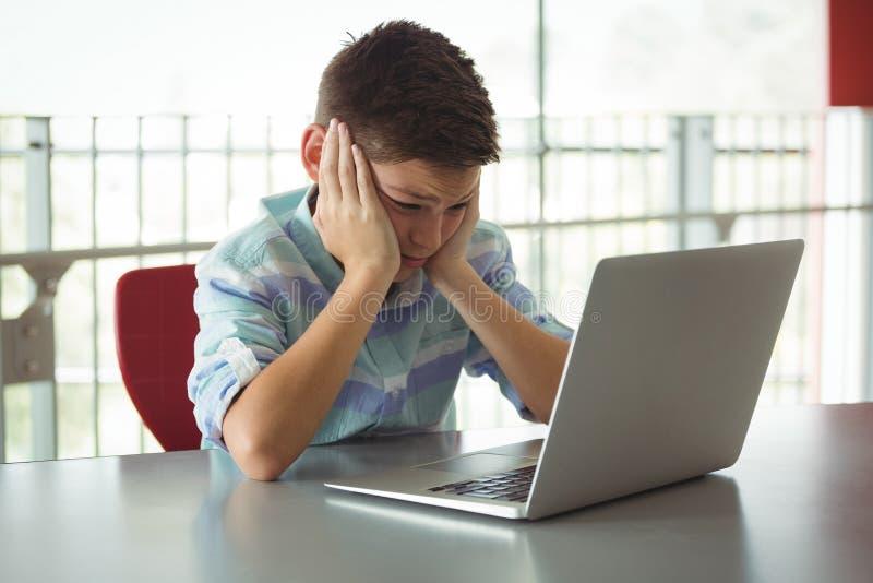 Scolaro triste che esamina computer portatile in biblioteca fotografia stock libera da diritti