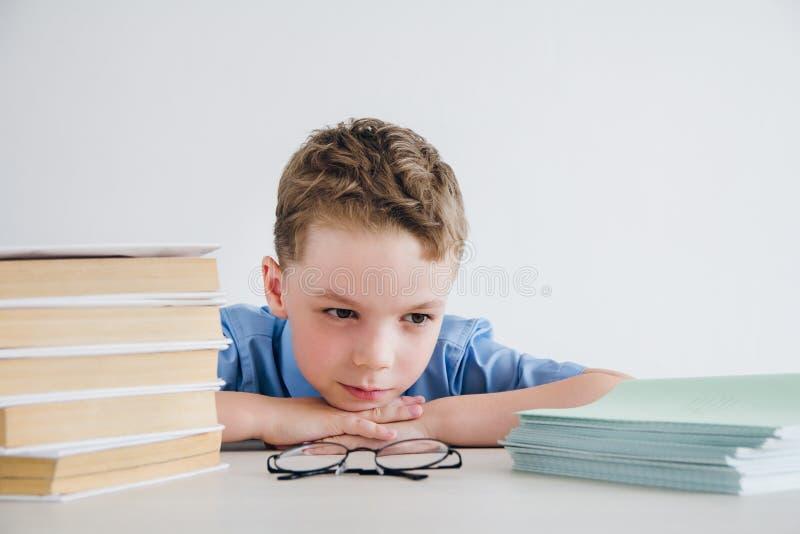 Scolaro in uniforme scolastico che si siede ad uno scrittorio con i manuali e fotografia stock libera da diritti