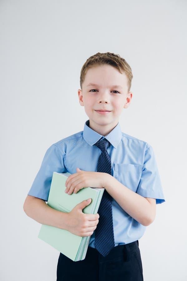 Scolaro in uniforme scolastico che tiene una pila di taccuini nel suo fotografia stock libera da diritti