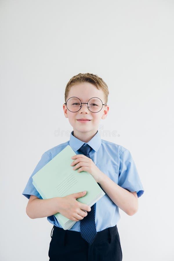 Scolaro in uniforme scolastico e vetri, tenenti una pila di nota immagine stock libera da diritti