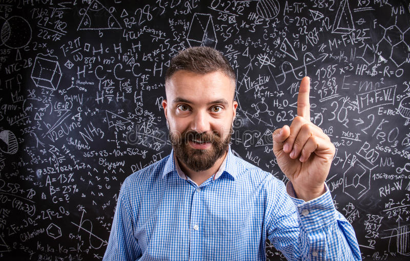 Scolding teacher against big blackboard with mathematical symbol stock photos