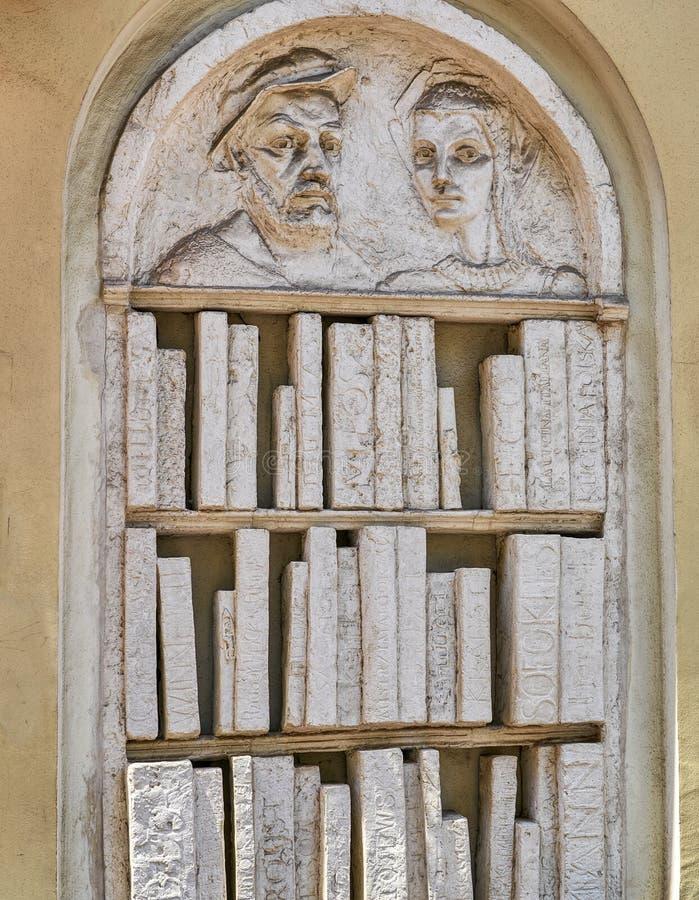 Scolpisca in rilievo di uno scaffale per libri con i libri fatti dalla pietra o intonachi fotografia stock libera da diritti