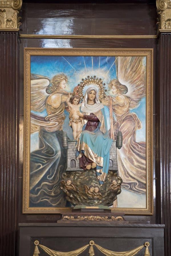 Scolpisca vergine Maria con il bambino Gesù e gli angeli dipinti fotografie stock