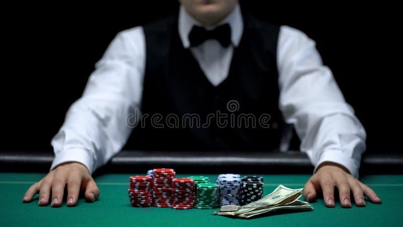 Scommessa aspettante, chip e soldi del commerciante del casinò trovantesi sulla tavola, affare di gioco fotografia stock