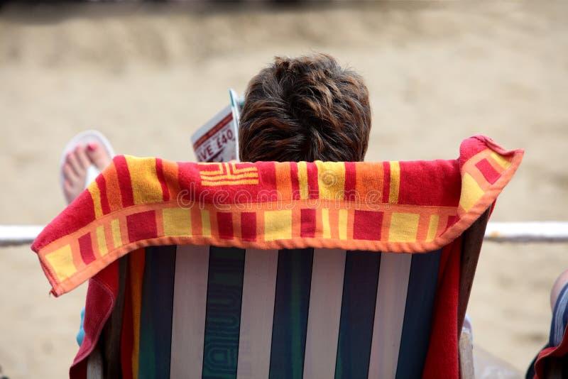Scomparto della lettura della donna sulla spiaggia nel deckchair immagini stock libere da diritti