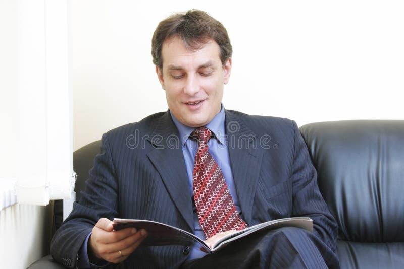 Scomparto sorridente della lettura dell'uomo d'affari fotografia stock