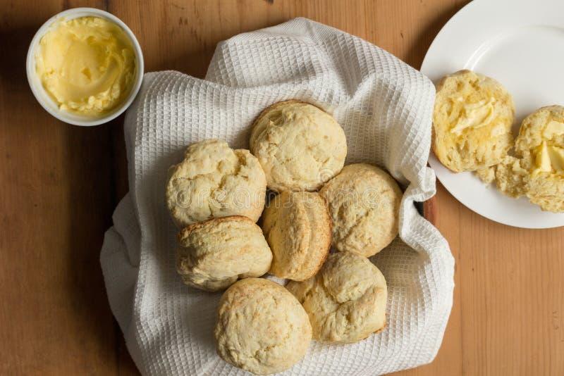 Scones в полотенце блюда с отрезанными scones, умасленными в плите на деревянном столе стоковое фото rf